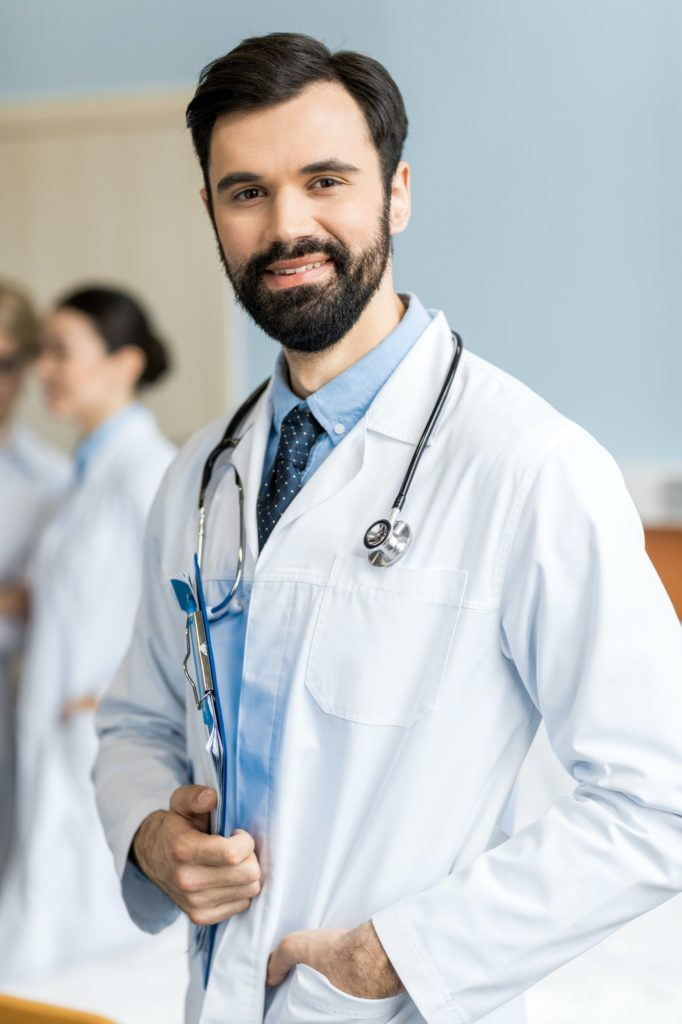 portrait of smiling doctor with doctor stethoscope and folder in clinic